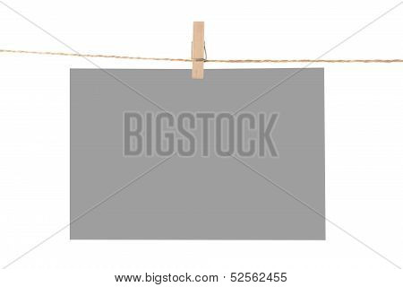 Photo paper attach to rope with clothes pins isolated on white background