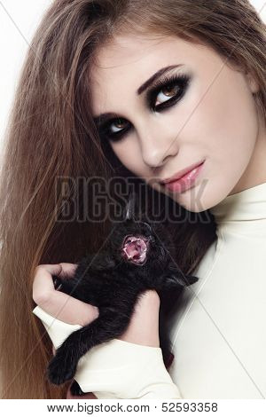 Portrait of young beautiful girl in latex catsuit with smokey eyes makeup and black kitten in her hands