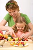 Little girl and her mom having fun preparing summer fruits salad poster