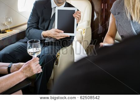 Cropped image of businessman showing digital tablet to colleagues in private jet