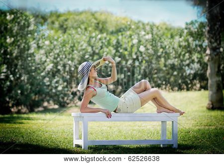 Young Woman Lying On Bench In Park