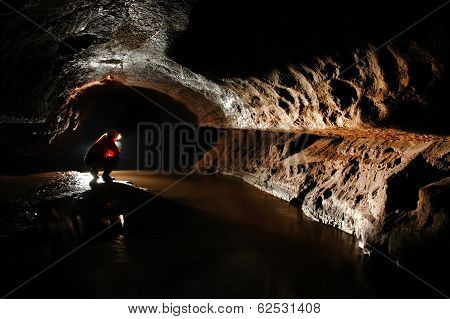 Spelunker exploring a river in a cave poster