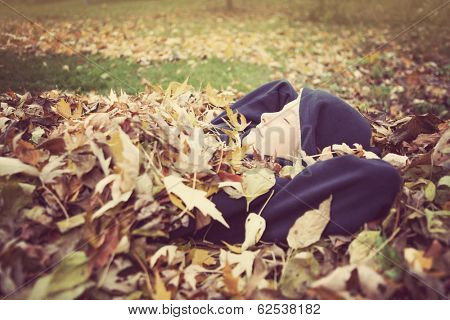 young boy laying in a pile of fall leaves
