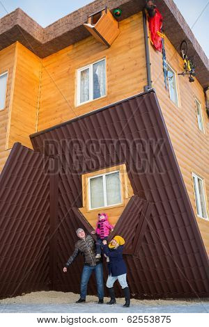 Family of three against the real inverted house
