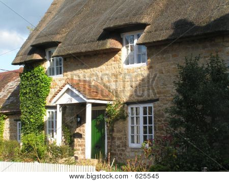 An English Thatched Cottage With Picket Fence