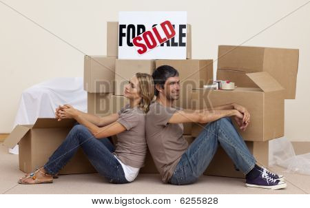 Happy Couple Sitting On Floor After Buying House
