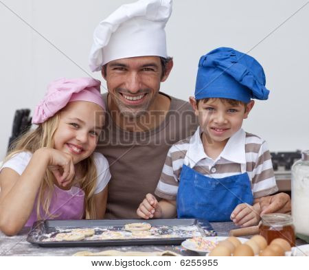 Happy Father And Children Baking Cookies Together