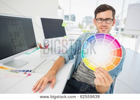 Portrait of a male artist holding color wheel by computer at desk