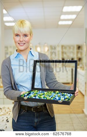 Smiling woman holding jewelry case in a jeweler store