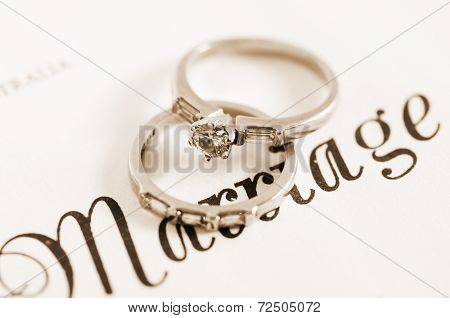 Sepia Vintage Retro Style Wedding And Diamond Engagement Rings On Marriage Certificate Closeup Macro