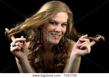 Beautiful girl wrapping her curly hair around both index fingers isolated on black