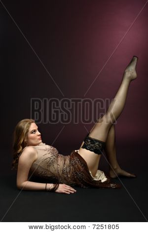 Sexy girl showing her legs in black stockings on dark red background