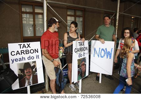 Tax carbon signs ready to march