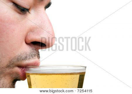A young man sipping a tall glass of beer isolated over white. Shallow depth of field with sharp focus on the lip and beer. poster