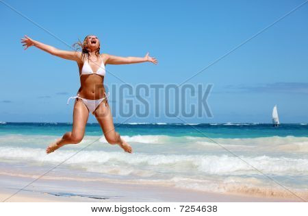 Young Woman Jumping On Tropical Beach
