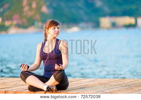 Young Girl In Lotus Listening To Music While Sitting On A Pier