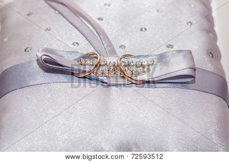 wedding rings on a satin pillow