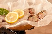 Close up of rainbow trout fish on antique weighing scales with lemon and parsley poster