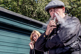 Man And Woman Standing Smoking E-cigarettes