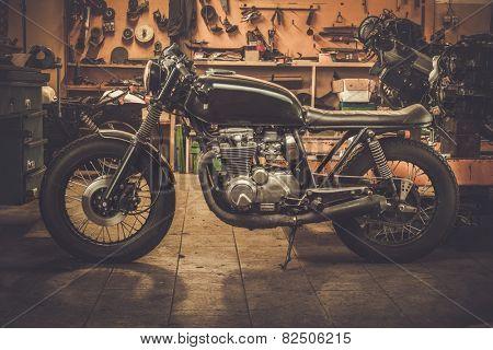 Vintage style cafe-racer motorcycle in customs garage