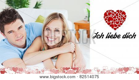 Smiling beatiful couple sitting on a sofa against ich liebe dich