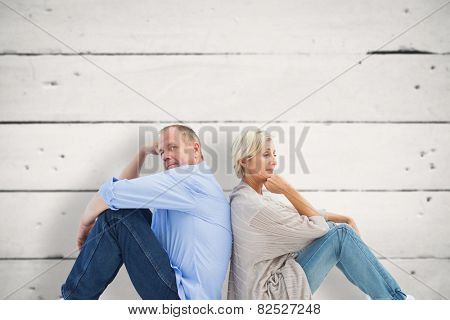 Upset mature couple not talking against white wood