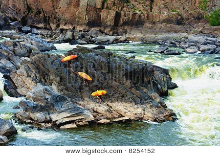 Kayakers Climbing Rock On River