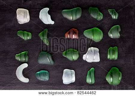 collection of old sea glass bottlenecks on blackboard background