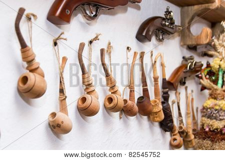 traditional wooden smoking tobacco pipe hanging on white wall