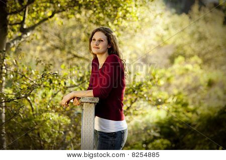 Woman pondering on wooden bridge