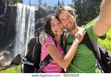 Selfie couple hikers at Yosemite National Park taking a self portrait picture with beautiful waterfall, Vernal Fall. Young hiking couple relaxing after hike in beautiful summer nature landscape.