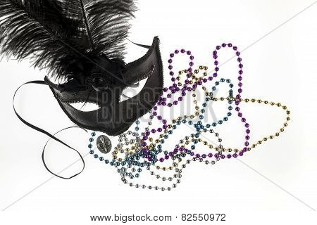 Shiny Gold, Purple, Blue And Silver Beads And Mardi Gras Mask With Feathers And Fleur D'lys On A Whi