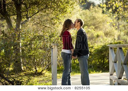 Couple kissing on wooden bridge