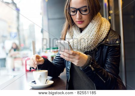 Beautiful Girl Using Her Mobile Phone In Cafe.
