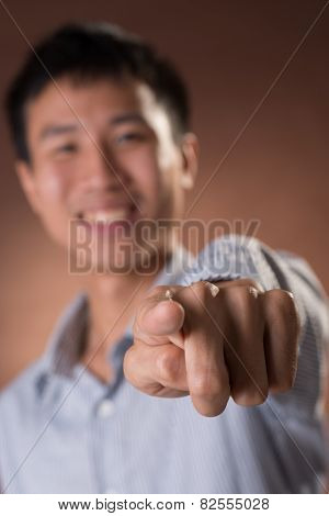 Young Chinese frank businessman point at you, focus on finger, closeup portrait in studio.