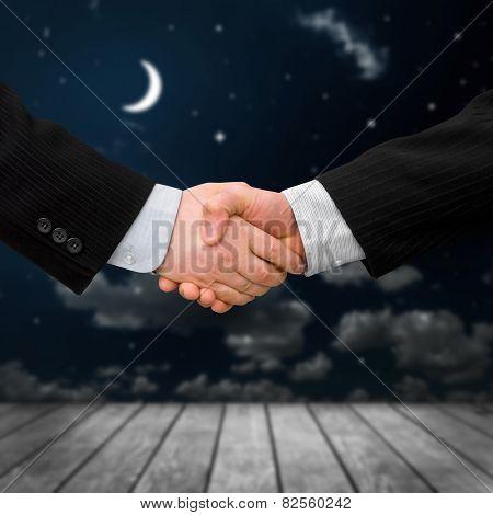 busines man handshake with night sky background