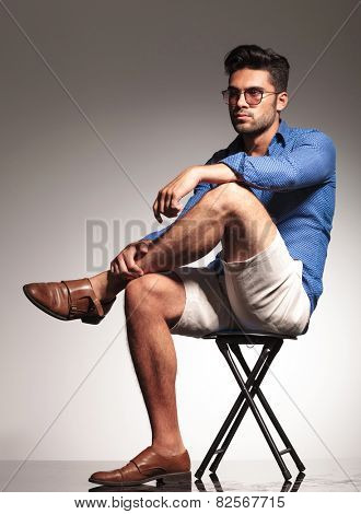 Smart casual young man sitting on a stool, resting his hand on his kne while looking away from the camera.