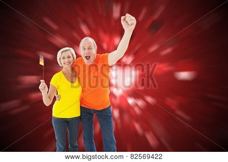 Happy german couple cheering at camera against valentines heart design