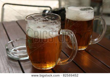 PRAGUE, CZECH REPUBLIC - MAY 13, 2014: Two mugs of traditional Czech beer Pilsner Urquell seen in a pub in Prague, Czech Republic. poster