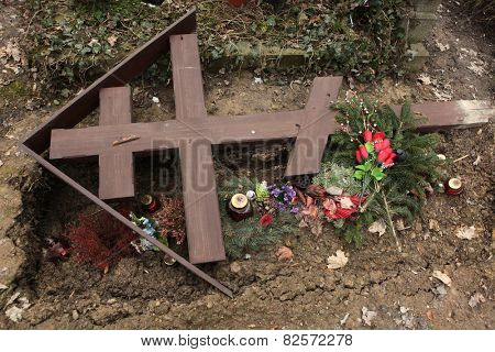 Fallen orthodox cross on an unmarked grave at the Olsany Cemetery in Prague, Czech Republic.