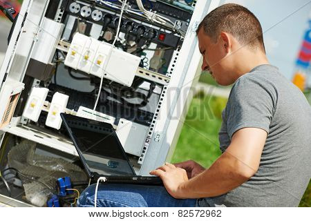 engineer working with laptop outdoors adjusting communication equipment in distribution box poster