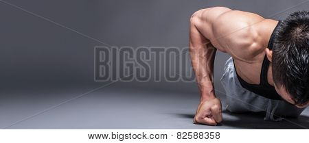 Young asian man workout over grey background with copy-space