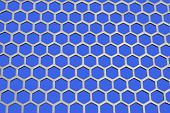 Aluminum honeycomb lattice in the form. Close-up. On a blue background poster