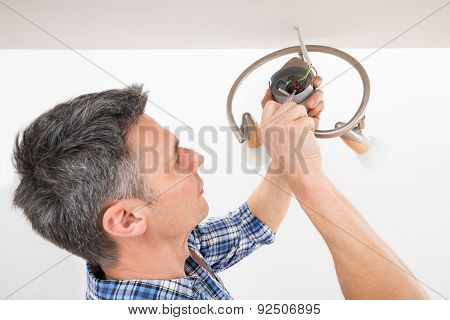 Electrician Fixing Light On Ceiling