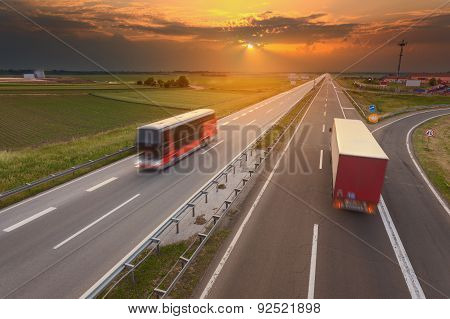 Truck And Bus In Motion Blur On Motorway At Sunset