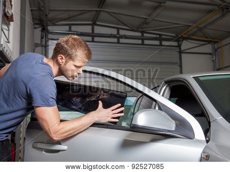 Applying tinting foil onto a car window in a workshop poster