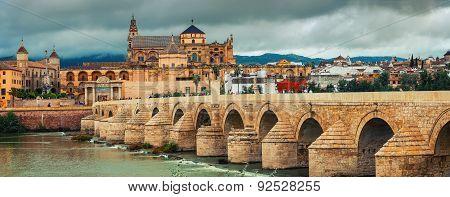 Roman Bridge Across The Guadalquivir River And La Mesquita Cathedral In Cordoba, Spain