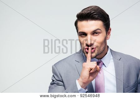 Businessman pointing finger over lips, asking for silence  over gray background. Looking at camera poster