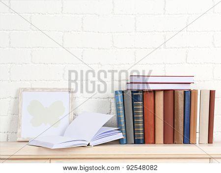 Books on shelf on wall background
