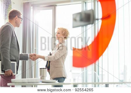 Creative business colleagues shaking hands in office